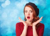 image of beret  - Redhead women in beret on blue background - JPG