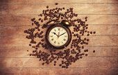 Alarm Clock And Coffee Beans On A Wooden Table.