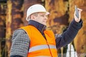Building inspector filmed with tablet PC near factory