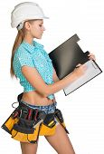 Woman in hard hat and tool belt writing on blank clipboard