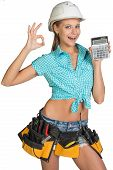 Woman in hard hat and tool belt showing calculator, making okay gesture