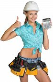 Woman in hard hat and tool belt showing calculator, giving thumb up