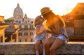 Mother And Baby Girl Kissing While Sitting On Street Overlooking Rooftops Of Rome On Sunset