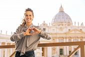 foto of state shapes  - Happy young woman showing heart shaped hands in front of basilica di san pietro in vatican city state - JPG