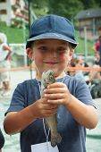 image of trout fishing  - happy child with a trout in his hand while fishing competition - JPG