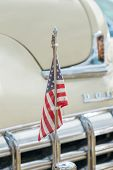 An American Flag Mounted On The Hood Of A Cream Dodge Coronet Classic Car