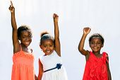 Three African Youngsters Raising Hands.
