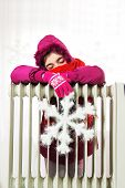 stock photo of freezing temperatures  - Freezing Young Girl in Winter Jacket Near a Heater - JPG