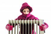 stock photo of freezing temperatures  - Young Girl in Warm Winter Jacket with Hood Near a Heater - JPG