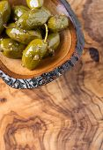 stock photo of kalamata olives  - Green olives marinated with coriander in small wooden bowl over olive wood board selective focus copy space top view - JPG