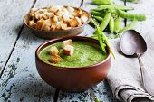 puree soup with green peas on a wooden surface