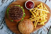 picture of hamburger  - hamburger with french fries and sauce on a wooden surface - JPG