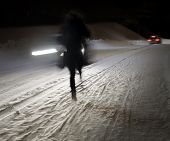 foto of slippery-roads  - Woman walking on winter road at night with cars in blurred motion - JPG