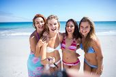 stock photo of selfie  - Happy friends doing pictures with selfie stick at the beach - JPG
