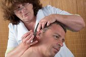 foto of pointed ears  - Woman acupuncturist prepares to tap needle around ears of man - JPG