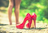 stock photo of stiletto heels  - Red high heel shoes on the ground with barefoot girl on background