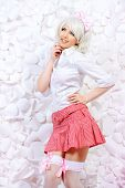 image of up-skirt  - Lovely girl wearing white wig and white blouse with plaid skirt posing over  background of white paper flowers - JPG
