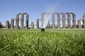image of aqueduct  - Grass Sprinklers wtih Roman Aqueduct of Merida at the bottom. Extremadura Spain