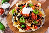 image of jalapeno  - Mexican nacho chips topped with sour cream ground meat jalapenos tomatoes beans and melted cheese on a wooden paddle board - JPG