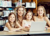 picture of mums  - Little girls and their mum with a laptop in library - JPG