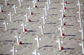 image of graveyard  - White crosses memorial graveyard symbols in sand. ** Note: Shallow depth of field - JPG