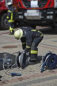 Постер, плакат: Firefighter Prepare Equipment