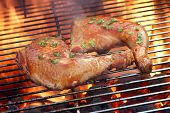 pic of flame-grilled  - Two Glazed Chicken Quarter On The Hot BBQ Charcoal Flaming Grill Close - JPG