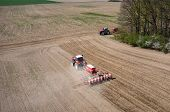 image of cultivator-harrow  - Aerial view of the the tractor harrowing the large brown field in spring season - JPG