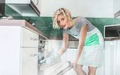 image of vapor  - Funny woman cook frying or roasting something in a oven - JPG