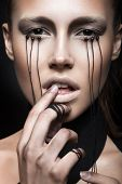 image of black eyes  - Beautiful girl with creative makeup in Gothic style and the threads of eyes - JPG
