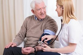 image of hypertensive  - Young smiling caregiver checking her older patient - JPG