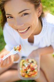 image of takeaway  - Woman eating gluten free pasta salad - JPG