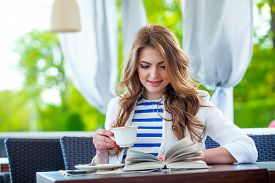 picture of cafe  - beautiful young girl in outdoor cafe reading a book and drinking coffee - JPG