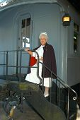 picture of caboose  - elderly lady stands on the steps of a caboose - JPG