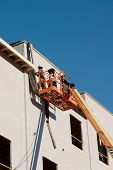 stock photo of cherry-picker  - two construction workers on a cherry picker working on a building under construction - JPG