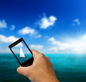 sailboat sky and cell phone in hand