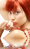 Redhead With Red Beads Looking Over Shoulder In Water