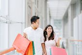 Happy Asian Couple Holding Colorful Shopping Bags And Enjoying Shopping, Having Fun Together In Mall poster