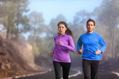 Runners training outside running on road - Two athletes couple jogging in nature wearing sportswear  poster