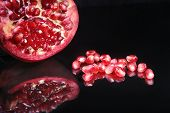 Pomegranate Seeds And Beautiful Ripe Pomegranate On Black Mirror Background With Place For Copy Spac poster