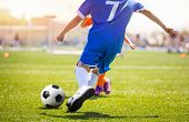 Football Player Running The Ball And Kicking Towards Opponents Goal. Soccer Stadium In The Backgroun poster