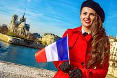 Bright In Paris. Elegant Traveller Woman In Red Trench Coat On Embankment In Paris, France With Fren poster
