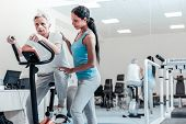 Training Legs. Concentrated Aged Grey-haired Man Exercising On A Training Device And Training His Le poster