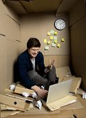 White Fury Concept. Full Length Of Young Annoyed Businessman Is Sitting Inside Small Cardboard Offic poster