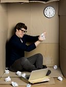 Full Of Fury. Young Businessman Is Sitting On Floor Of His Cramped Carton Office And Shredding Docum poster