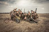 Men Hunters Group Team Portrait In Rural Field Posing Together Against Overcast Sky During Hunting S poster
