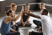 Smiling Diverse Yoga Team Members Giving High Five At Group Class, Fit Sporty Young African And Cauc poster