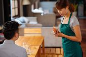 Young Vietnamese Waitress Taking Order In Cafe poster