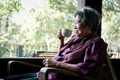 Asian Elder Woman Holding Tea Cup On Terrace. Elderly Female Relaxing On Patio. Senior Drinking Coff poster