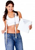 Woman loosing weight in baggy clothes and holding a scale - isolated over white